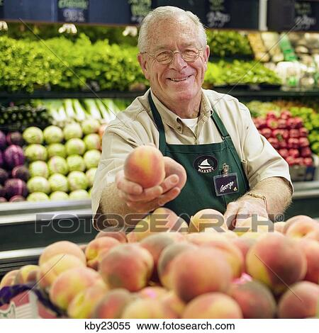 Stock Image of Mature grocery clerk working in produce ...