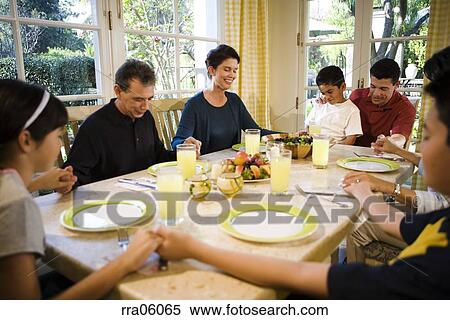 Stock Image of Multi-generation family saying prayer at ...