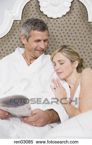 stock image of couple laying in bed ren03085 search stock photos mural pictures photographs. Black Bedroom Furniture Sets. Home Design Ideas