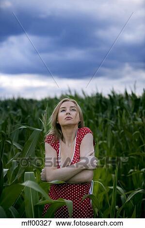 Picture of Woman in corn field shivering, portrait ...