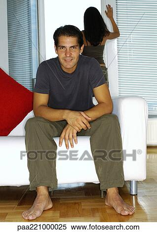 Stock Image Of Man Sitting On Sofa Woman Looking Out Of