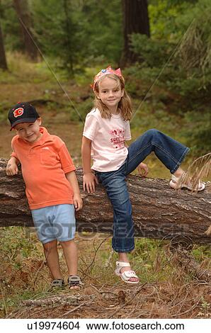 Stock Photo of Two children climbing over a log u19974604 ...