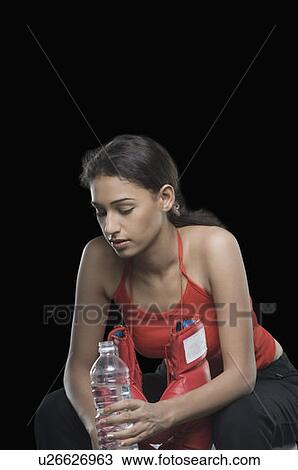 Stock Photo of Young woman holding a water bottle and ...