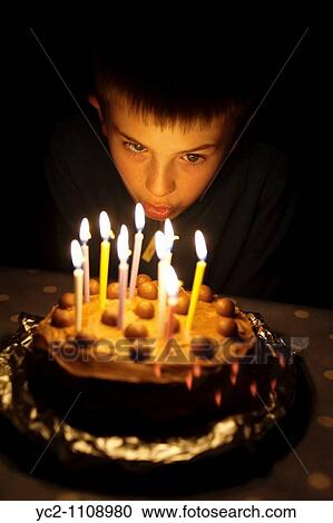 A Picture Of Ten Year Old Boy Blowing Out The Candles On His Birthday Cake In Uk
