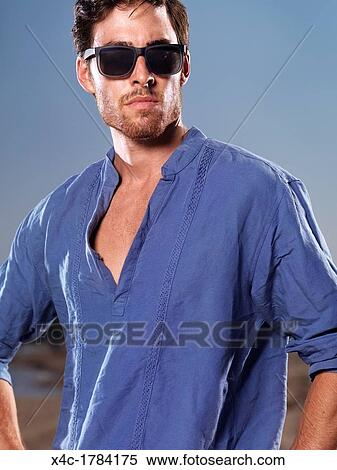 c1589a4f860f Stock Photography - Fashion portrait of a young man in blue shirt and  sunglasses at the
