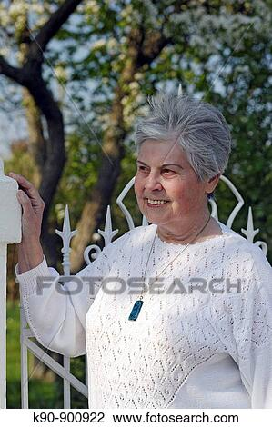 Half Body Image Of Elderly Caucasian Woman Wearing A White Sweater At Sunny Weather Looking Friendly And With Blossoming Tree In The Background