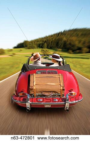Stock Photography Of Middle Aged Couple On Tour In A Vintage Porsche