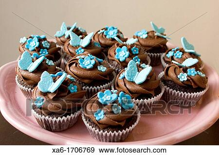 Pink Plate Of Cupcakes With Chocolate Frosting Swirl And Blue