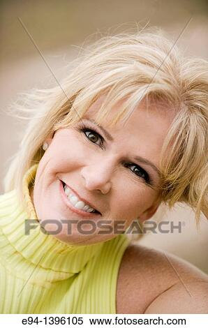 Portrait Of A 50 Year Old Blond Woman In An Outdoor Setting Smiling
