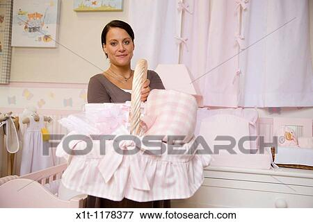 c70d65c5a Pregnant woman holding basket of baby clothes. Stock Photo | x1t ...