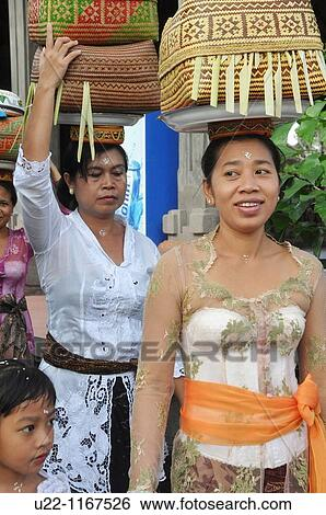Ubud Bali Indonesia Women In Traditional Dress Carrying A Basket With Offerings On Their Heads Going To A Ceremony In A Hindu Temple Stock
