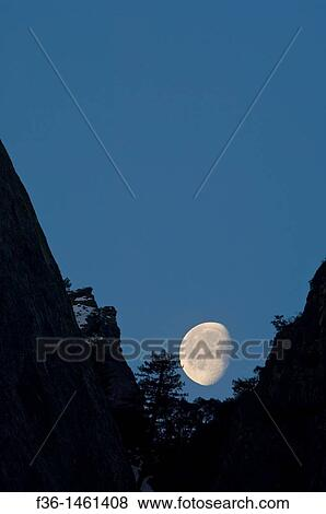 Pictures Of Waning Gibbous Moon Setting Behind Mountain Cliff