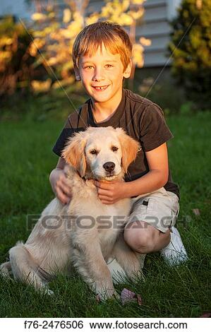 Smiling 12 year old boy holding his golden retriever puppy