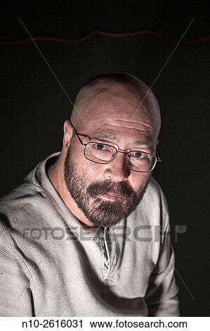 Età media uomo calvo con uno barba e glasses archivio