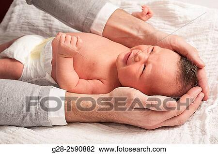 Little baby boy smiling, 2 weeks old, between his father's arms and hands,  trying to soothe him, and protect him;