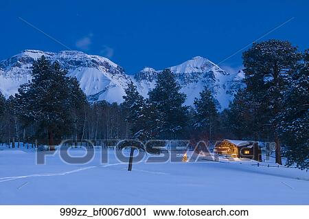 Christmas In Colorado Mountains.Winter Scenic Of A Rustic Cabin With Christmas Lights And Lit Christmas Tree At Dusk And San Juan Mountains In The Background Ridgeway Colorado