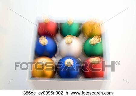 colorful christmas tree bulb ornaments stacked in box on white background studio portrait