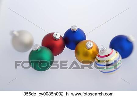 multiple colorful christmas tree bulb ornaments on white background with blue tint studio portrait