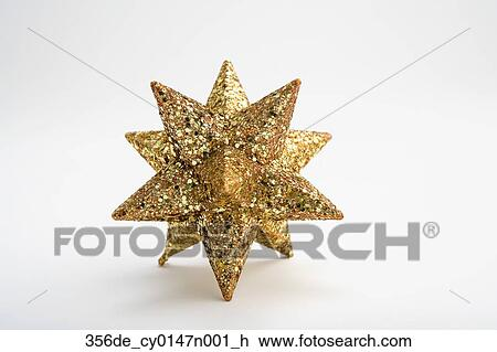 Stock photo of one gold christmas start ornament blurred on white
