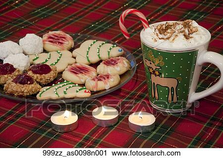closeup of homemade christmas cookies arranged on glass plate on a red plaid tablecloth with hot chocolate drink off to the side - Homemade Christmas Cookies