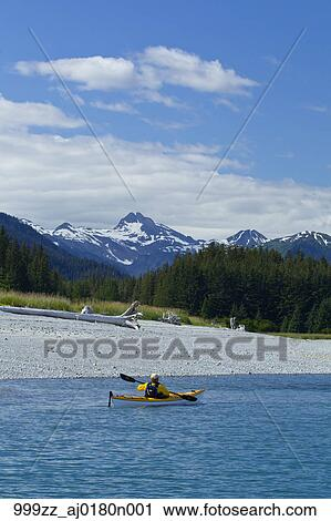 e22ccc844 Sea kayaker paddles along the shoreline near Juneau with Chilkat Mountains  in the background