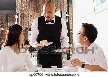 stock images of couple in restaurant waiter standing holding