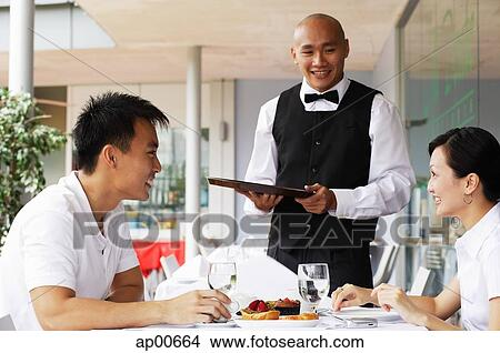 stock photo of couple in restaurant waiter standing next to their