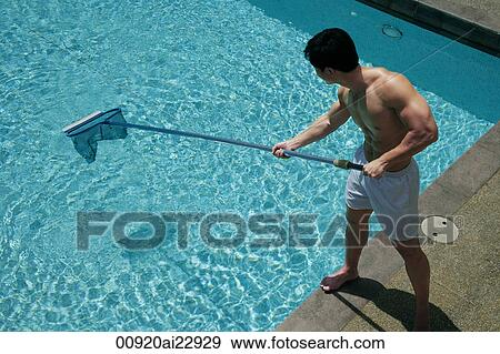 Young man cleaning swimming pool Stock Photo