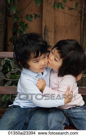 Stock Photo Of Young Girl Kissing Young Boy Cheek 01350ai23394