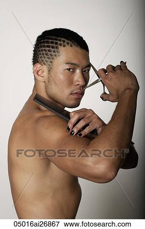 Picture Of Young Man With No Shirt Holding Scissors And Comb