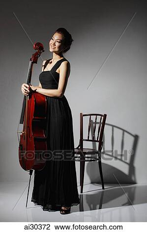 Stock Photo Of Woman In Long Black Dress Holding A Cello And Smiling