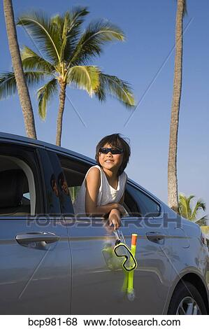 Boy Holding A Scuba Mask And Snorkel Leans Out Car Window
