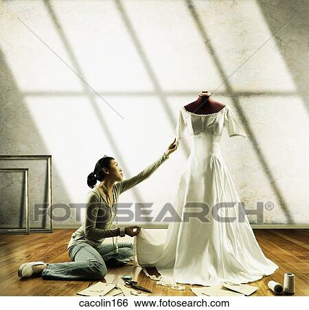 Stock Images of Young seamstress working on a wedding gown on a ...