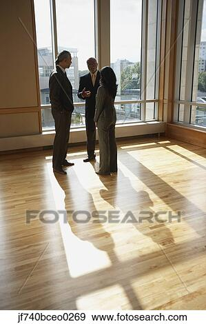 Three businesspeople talking in sunlit room, North Bethesda, Maryland,  United States Stock Photo