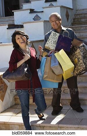Asian Man Carrying Ping Bags For Wife