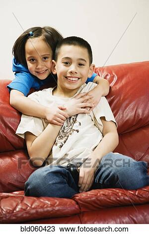 stock photo of asian siblings hugging on sofa bld060423 search