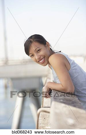 stock photo of asian woman leaning on railing bld068243 search
