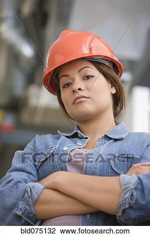 stock photo of serious hispanic woman wearing hard hat with arms