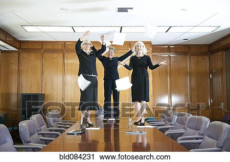 Stock Photography Of Businesswomen Standing On Table And Throwing - Standing conference room table