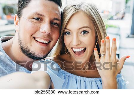 Smiling Caucasian Couple Posing For Selfie With Engagement Ring