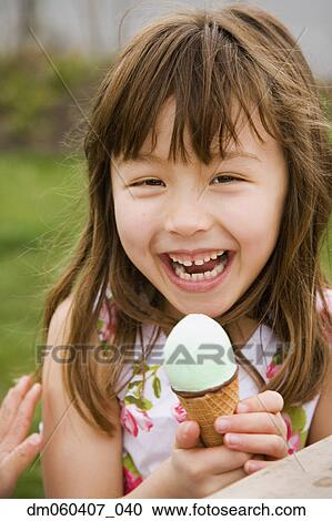 stock photography of young asian girl eating ice cream cone