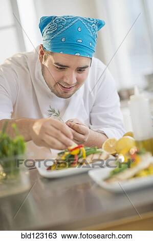 Mixed race chef plating food in restaurant Stock Image
