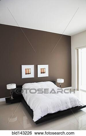 Wall art, lamps and bed in modern bedroom Stock Photograph ...