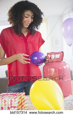 stock photo of mixed race woman inflating helium balloons for party