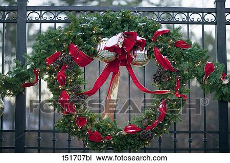 Christmas Decorations Hanging On A Fence Outside A Gated Community