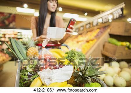 picture woman checking shopping list in grocery store fotosearch search stock photography