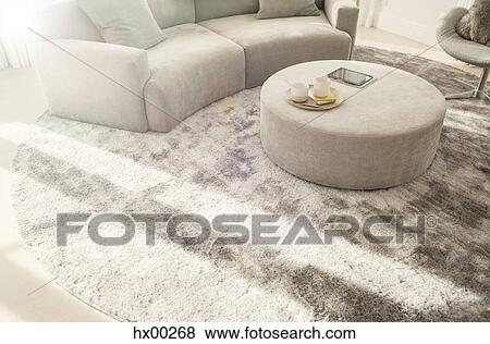 Round Rug Under Curved Sofa And Ottoman In Living Room Stock