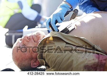 Rescue worker using defibrillator on unconscious car accident victim Stock  Photography