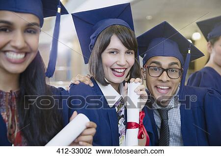 a45779f5f07 Portrait enthusiastic college graduates in cap and gown posing with diploma