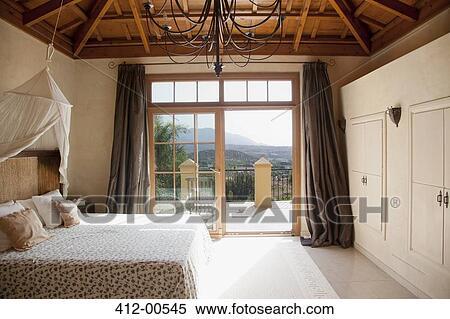 bed met baldakijn en frans deuren leidinggeven om te balkon in slaapkamer